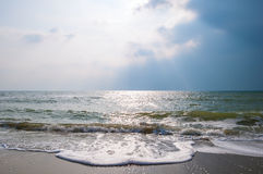 Sea waves on a sandy beach with stormy sky Stock Photo
