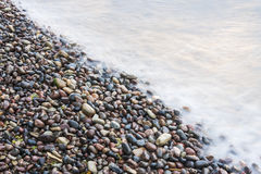 Sea waves on small rocks at seashore Stock Images