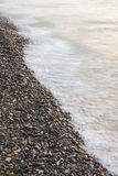 Sea waves on small rocks at seashore Stock Image