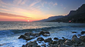 Sea waves with splashes break about stones  at sunrise stock video