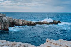 Sea waves splashing against rocky coastline. Dramatic cloudscape before sunderstorm royalty free stock photo