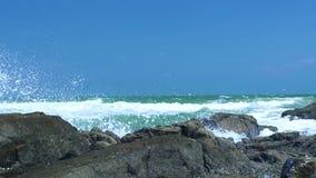 Sea waves splashing on rocky beach on blue sky landscape. Close up water waves breaking on stony coast in ocean. Blue. Sea waves splashing on rocky beach on blue stock video footage