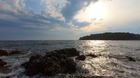 Sea waves on stone coast against cloudy sky, sun and island. Sea waves on stone coast against blue cloudy sky, sun and island with green trees. Sea foam washing stock video footage