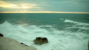 Sea waves wash against the shore. Turbulent sea splashing the coastline with waves on a cloudy day stock video footage