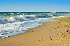 Sea waves wash the beach against a blue sky Royalty Free Stock Photos