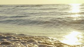 Sea waves washes sand beach at sunset. Calm surf image.  stock footage
