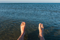 Sea waves washing man`s feet. Man relaxing on the beach Stock Photo
