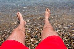 Sea waves washing man`s feet Royalty Free Stock Photography