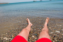 Sea waves washing man`s feet. Man relaxing on the beach Royalty Free Stock Image