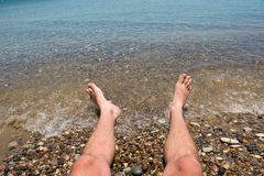Sea waves washing man`s feet. Man relaxing on the beach Royalty Free Stock Images