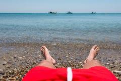 Sea waves washing man`s feet. Man relaxing on the beach Stock Image