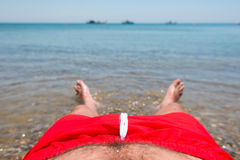 Sea waves washing man`s feet. Man relaxing on the beach Royalty Free Stock Photography