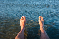Sea waves washing man`s feet. Man relaxing on the beach Royalty Free Stock Photos