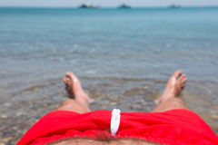 Sea waves washing man`s feet. Man relaxing on the beach Royalty Free Stock Photo