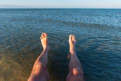 Sea waves washing man`s feet. Man relaxing on the beach. Sea waves washing man`s feet Stock Photo