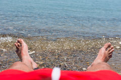 Sea waves washing man`s feet. Man relaxing on the beach Stock Images