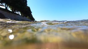 Sea waves washing seaside resort beach, under and over water. Sea waves with foam washing seaside resort stone beach, blue sky. Underwater splash of ground swell stock video footage
