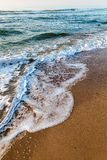 Sea waves in the white foam on the sandy beach. Dawn Stock Photos