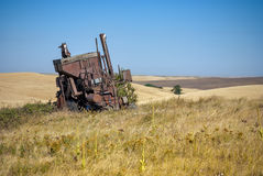 In a sea of wheat an old combine rusts Stock Image