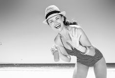Smiling modern woman on seacoast applying sun cream Royalty Free Stock Image