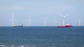 Sea wind farm turbines and ships in Aberdeen, renewable energy. Scotland