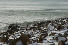 Sea in winter. Snow covered shingle beachin a gloomy day stock photos