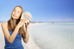 Sea and Woman listening conch Stock Image