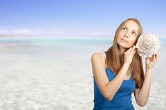 Sea and Woman listening conch Stock Photo