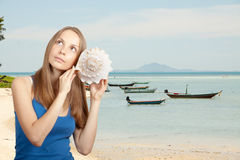 Sea and Woman listening conch Royalty Free Stock Photos