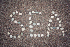 'Sea' word on the sand. Written with pebbles. Aged photo. Stock Photo
