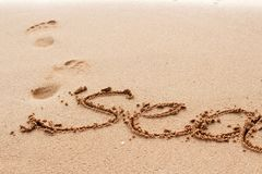 Sea word written on the sand. Sea word handwritten on the sand with footprint on background. Selective focus Stock Photo