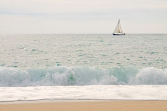 Sea, yacht, sky with wave and beach in foreground Stock Photos