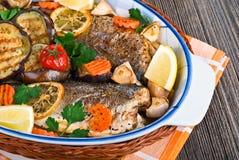 Seabass ψάρια που ψήνονται με τα λαχανικά, κινηματογράφηση σε πρώτο πλάνο Στοκ Φωτογραφία