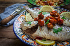 Homemade seabass with parsley. Seabass baked on oven with salad and lemon Stock Images