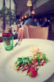 Seabass carpaccio on restaurant table, toned Stock Image