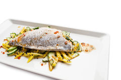 Seabass fillet served on a white plate. Seabass fillet served with cucamber and potato on a white plate Royalty Free Stock Image