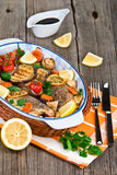 Seabass fish baked with vegetables, herbs and lemon Stock Photo