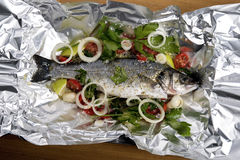 Seabass in tin-foil ready to baked. Seabass in parcel ready to baked Stock Image