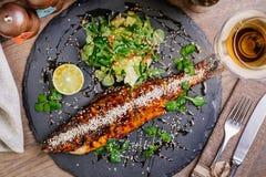 Seabassen grillade på en platta med grönsaker och citronen för mig Royaltyfria Foton