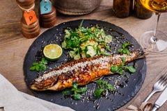 Seabassen grillade på en platta med grönsaker och citronen för mig Royaltyfri Foto