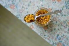 Seabuckthorn misto con il primo piano del miele in un cucchiaio sopra un barattolo Fotografia Stock