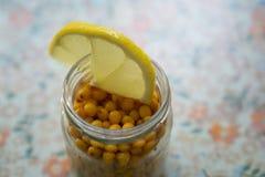 Seabuckthorn in un barattolo con la fetta del limone sopra il barattolo Fotografie Stock