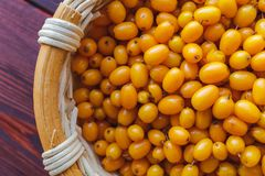 Seabuckthorn in a wooden basket. Top view, close-up Stock Image