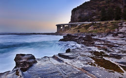 Seacliff bridge sunset. Australia NSW grand pacific drive sea cliff bridge at sunset low tide coastal seascape with sunlights and surfing waves Royalty Free Stock Photos