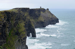 Seacliffs in Ireland. Irish sea cliffs and Moher Tower at Hag`s Head in Ireland during a storm Stock Images