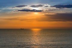 Seacoast linia horyzontu z pięknym zmierzchem nad małym statkiem w oceanie Zdjęcia Royalty Free