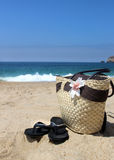 Seacoast, straw beach bag and flip-flops Stock Photos