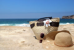 Seacoast, straw beach bag, hat and sunglasses Stock Photos