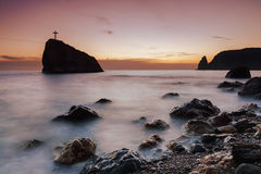 Seacoast at sunset and a cross on a rock Royalty Free Stock Images