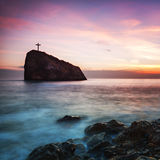 Seacoast at sunset and a cross on a rock Stock Images